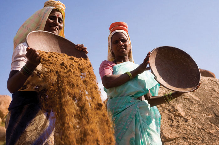 Two Indian women sifting through dirt