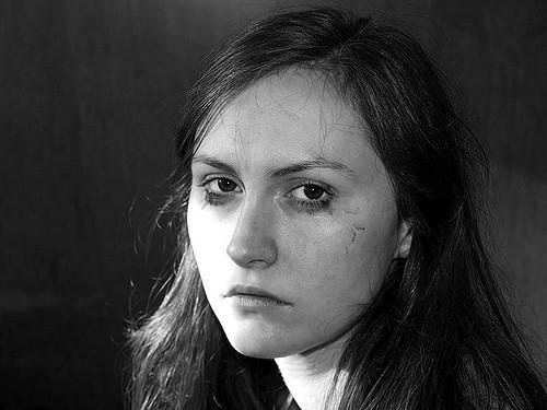 A woman with bleeding mascara staring at the camera,