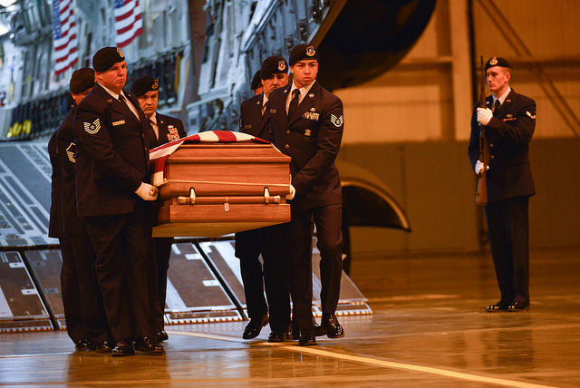 Members of the national guard carrying a casket of one of their fellow fallen, perhaps by suicide due to what was seen in the Iraq or Afghanistan War