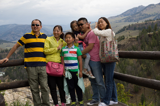 An Asian American family posing by a cliff on a family vacation