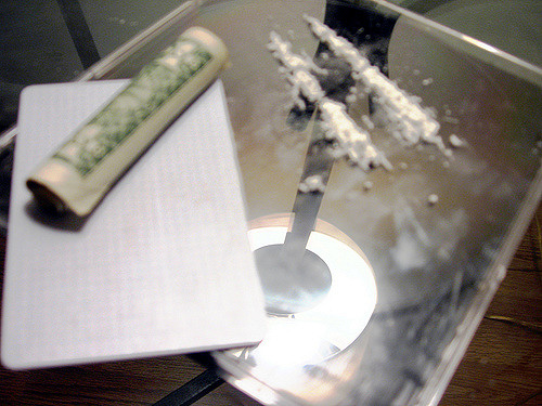 Two lines of cocaine on a mirror with a dollar bill rolled up next to it.