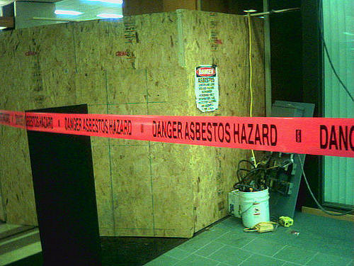 A construction zone with a red tape across it reading: Danger Asbestos Hazard