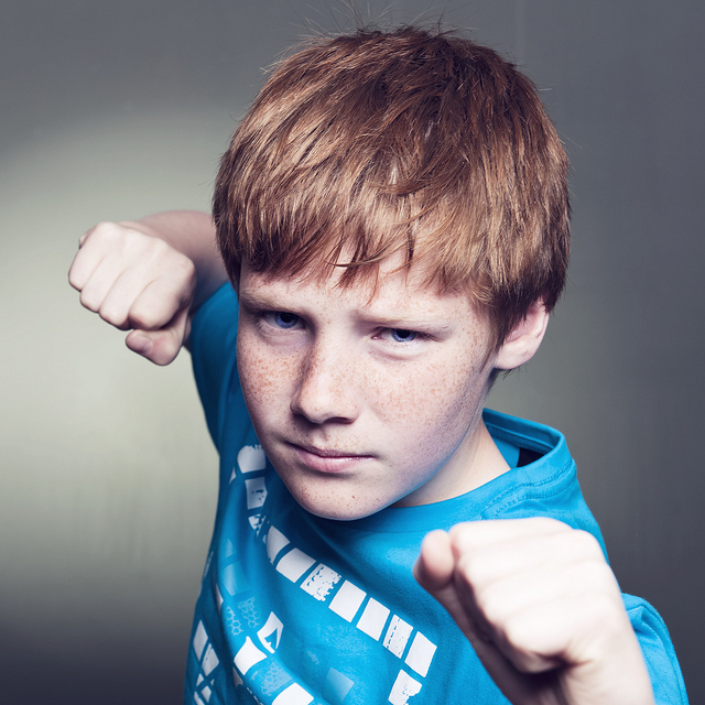 A young boy posing with his fists up towards the camera