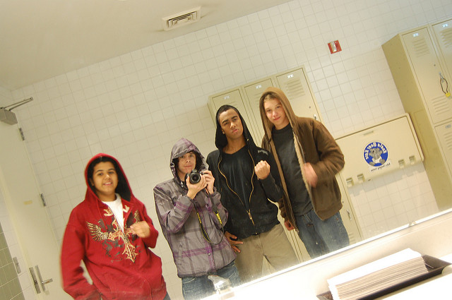 Four rough looking male students taking a picture with their hoodies on in the bathroom mirror