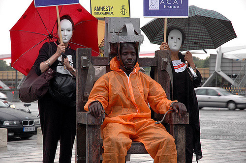 Three people protesting the death penalty and how it is racially discriminative. A black man sits in a mock electric chair, while two women wearing white masks stand watching.