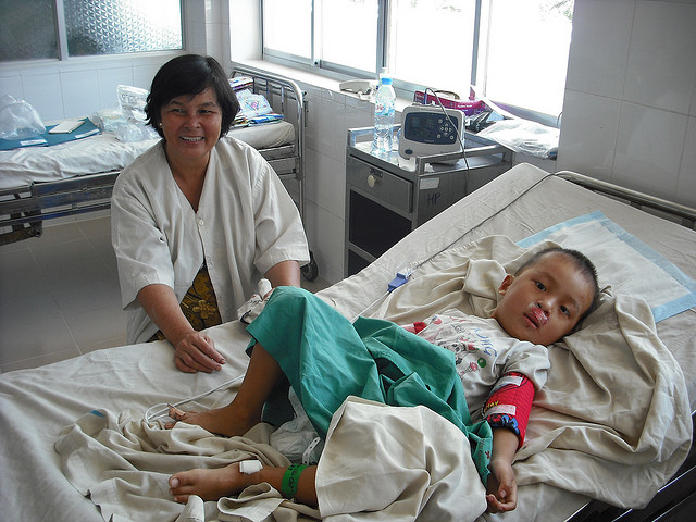 A nurse working with a child on a hospital bed