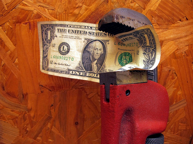 A wrench with a dollar being clenched