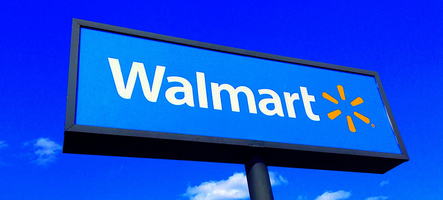 A tall Walmart sign against a clear, blue sky
