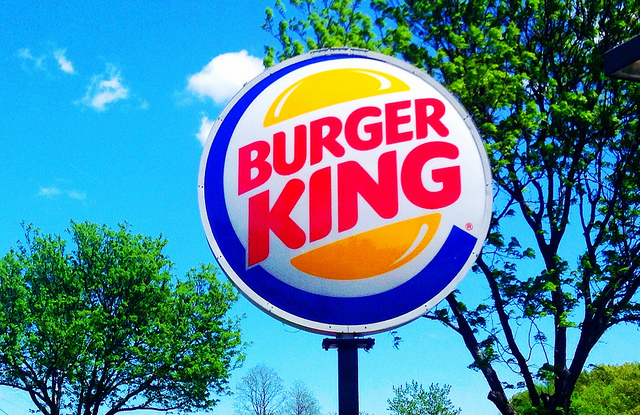A burger King sign amongst the trees and clear sky