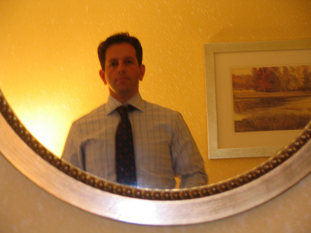 A man trying looking in a mirror while trying on a suit before his interview