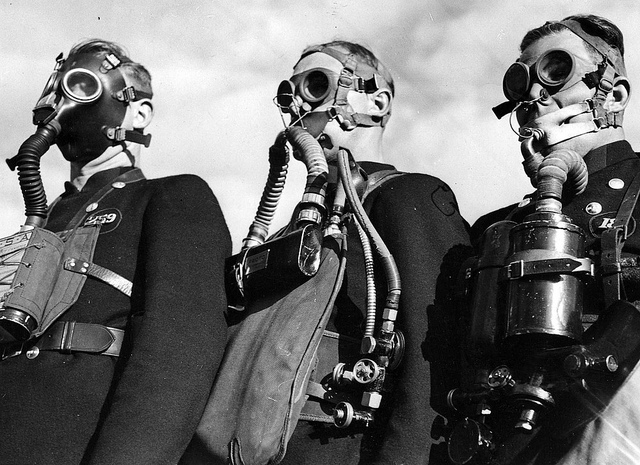Men wearing gas masks and protective clothing