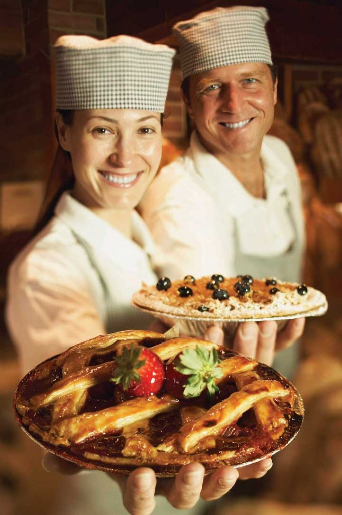 Two bakers showing off their pies