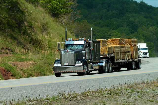 A semi truck hauling a bunch of lumber