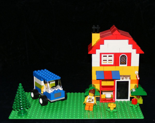 A Lego House with a car and two happy people
