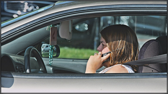 A woman using her cell phone while driving