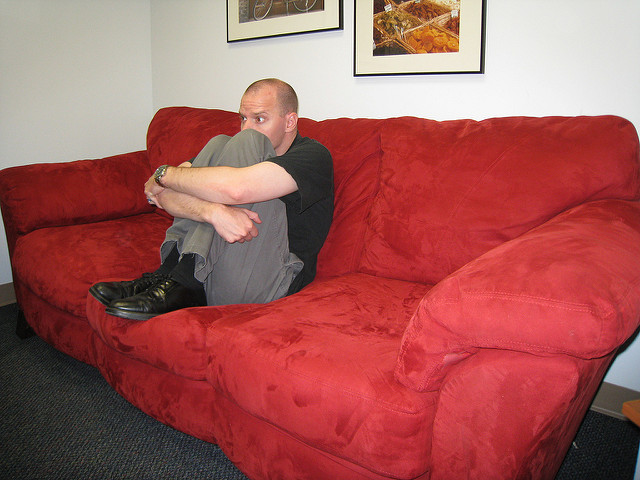 A man sitting in the fetal position on a couch