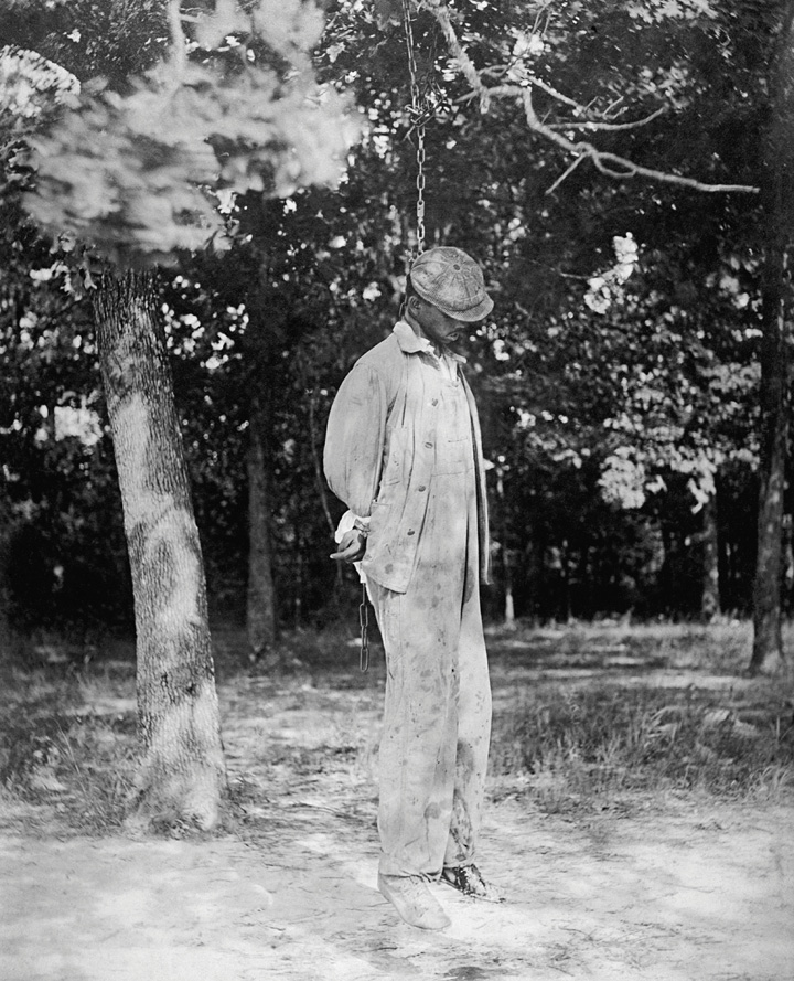 A picture of a lynched man hanging in a noose