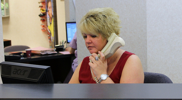 A woman receptionist answering a phone at Suburban Eye Care