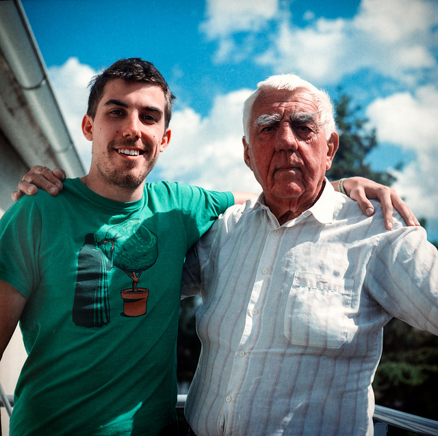 A grandson standing with his arm around his grandpa