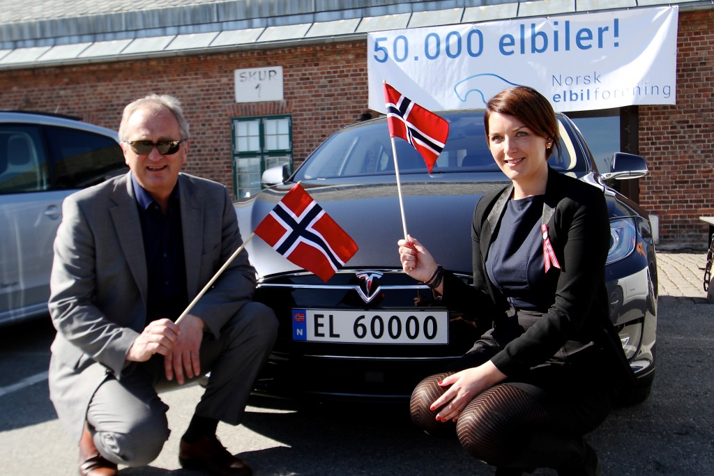 An older man standing next to a younger woman. They are both holding Norwegian flags next to a Tesla car.