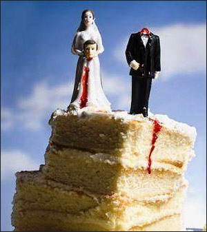 A slice of wedding cake with a groom and wife figurine. The wife figurine is holding the head of the groom in her hands