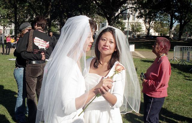 A newlywed lesbian couple both in wedding dresses