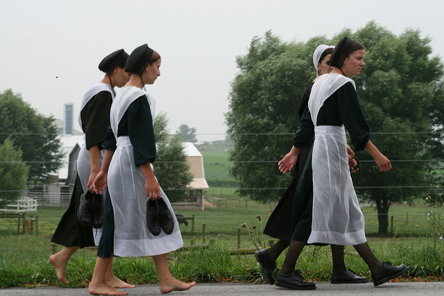 Four Amish women walking along the side of a road