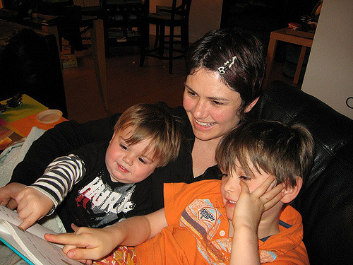A mother reading to her two young boys