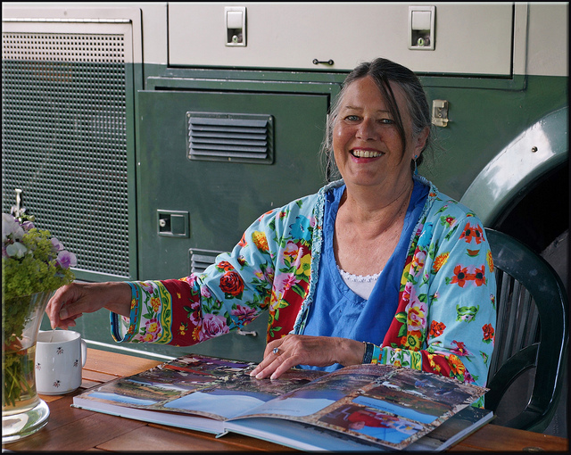 A woman in a colorful shirt looking at a scrapbook