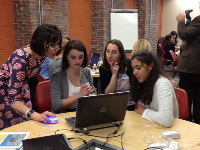 A teacher helping a group of students on a laptop