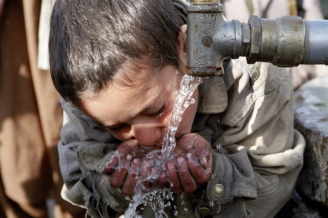 A child drinking water from a faucet