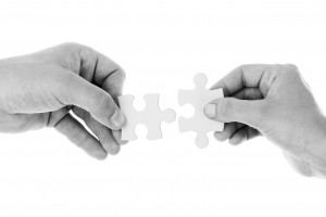 Two people trying to fit two puzzle pieces together