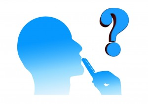 A silhouette of a man with a phone rested on his lips and a question mark in the air