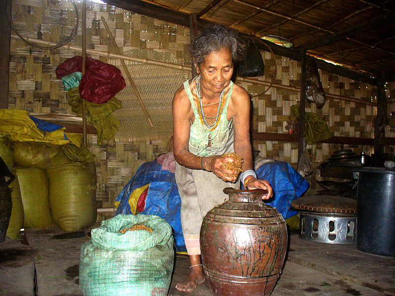Brao woman making rice wine in a jar