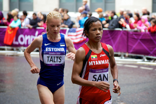 Two runners (one from Estonia and one from Myanmar) running at the Olympics
