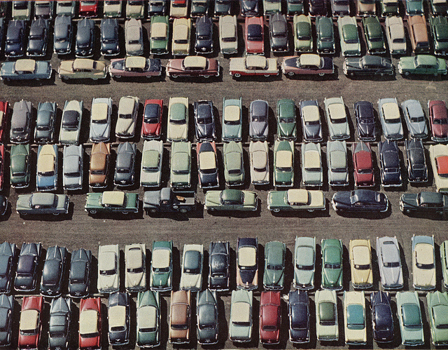 A parking lot with many parked in cars