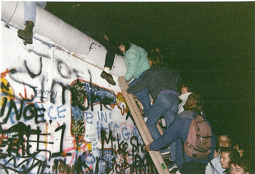 People gathering around the Berlin Wall, ready to take it down