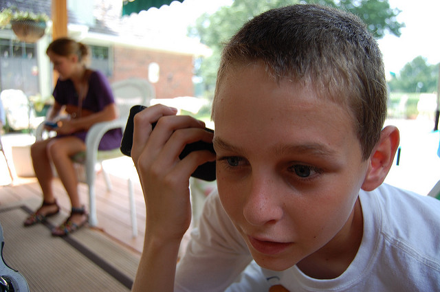 A child listening to an iPhone's speaker