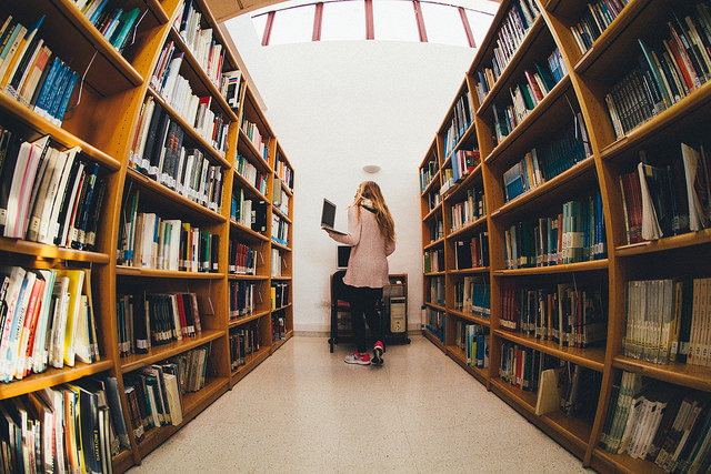 A young student doing research in a library