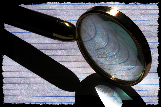 A magnifying glass zooming in on a lined sheet of paper