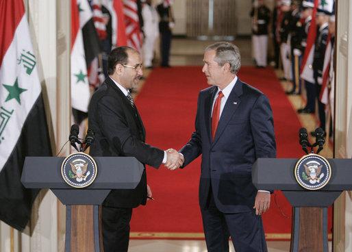 President George W. Bush shaking hands with Al Maliki