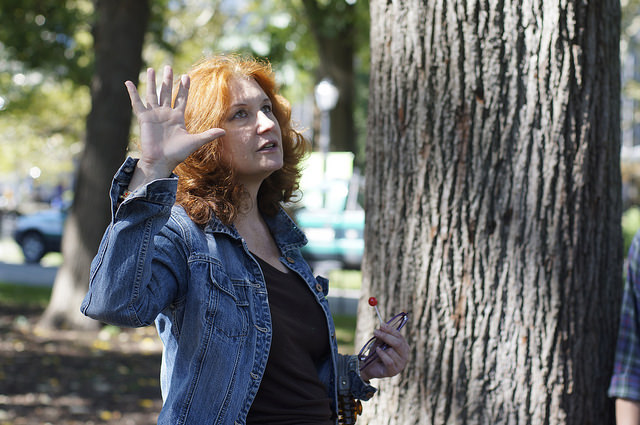 Karen Finley standing by a tree