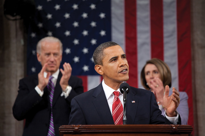 President Barak Obama giving a speech. Behind him is Joe Biden and Nancy Pelosi