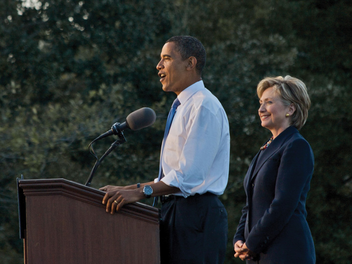 President Barack Obama giving a speech with Hillary Clinton standing behind him