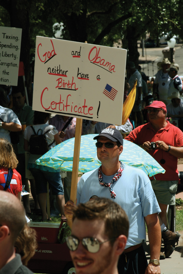 A tea party rally where a man holds a sign that says
