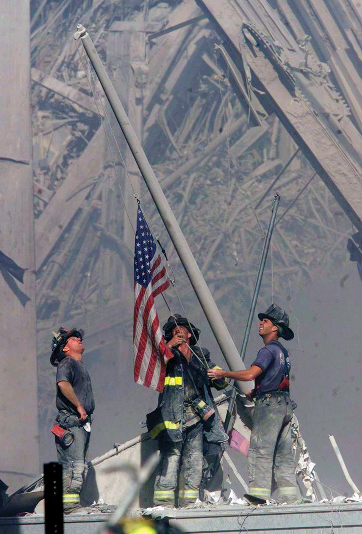 Soldiers raising a flag at the site where the Twin Towers had fallen