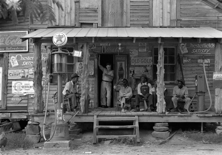 Men sitting out on the porch of an old wooden cabin