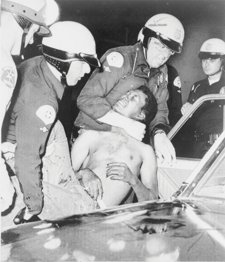 White cops detaining a black man during the Watts Riots