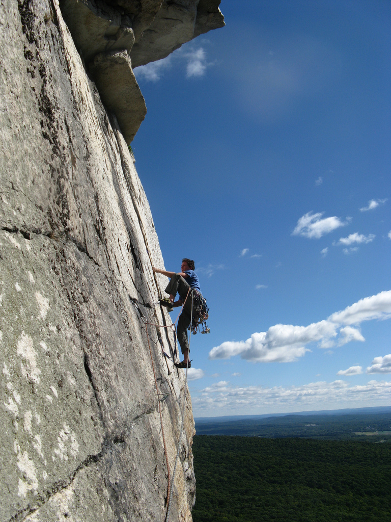 A man climbing a sheer rock cliff
