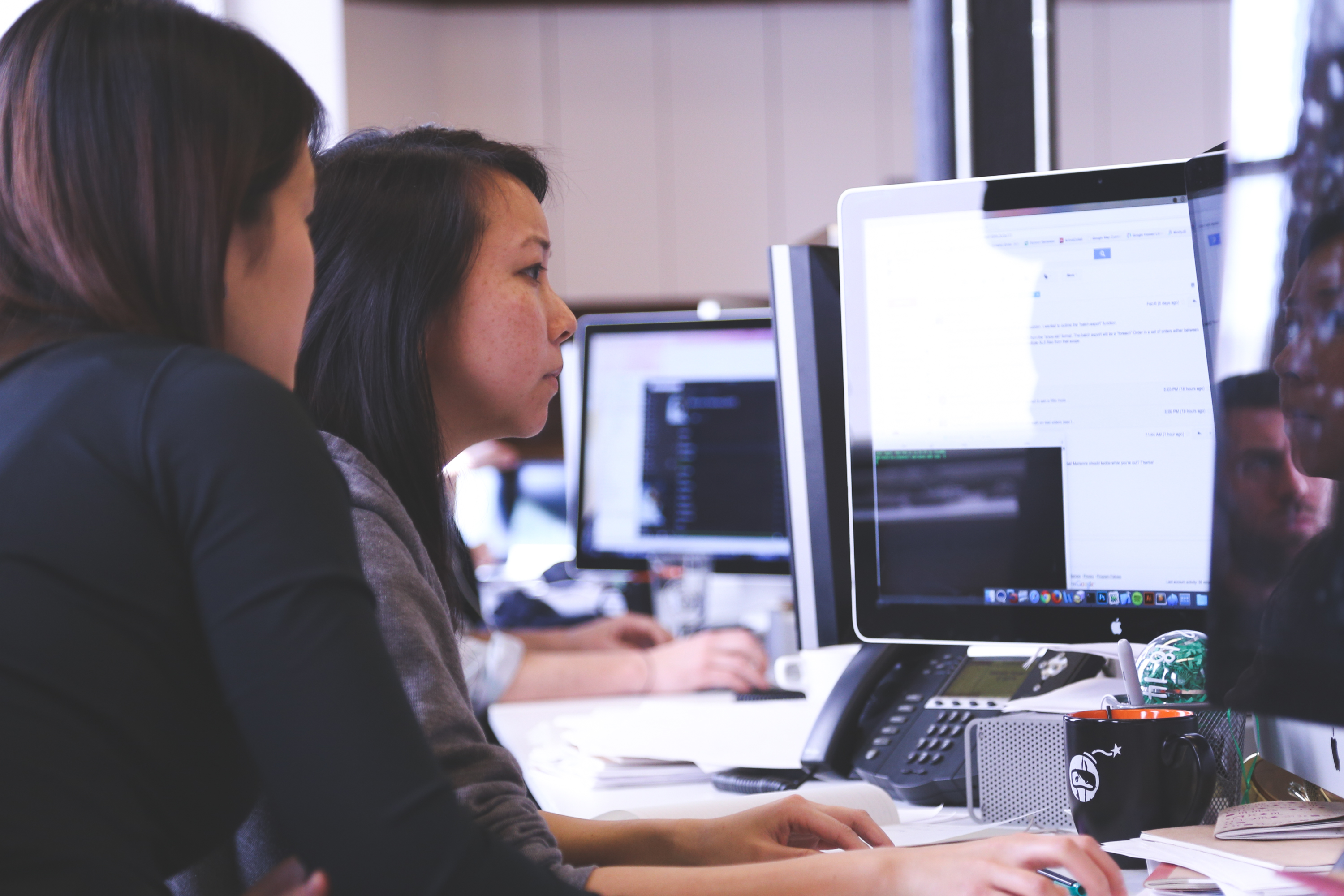 A woman helping a fellow coworker whil she works on a computer
